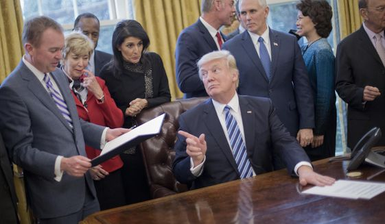 "President Donald Trump looks over towards Budget Director Mick Mulvaney, left, after signing an executive order in the Oval Office of the White House in Washington, Monday, March 13, 2017. Trump signed ""Comprehensive Plan for Reorganizing the Executive Branch"". From left are, Mulvaney, Small Business Administration Administrator Linda McMahon, Housing and Urban Development Secretary Ben Carson, UN Ambassador Nikki Haley, Interior Secretary Ryan Zinke, Vice President Mike Pence, Transportation Secretary Elaine Chao and Commerce Secretary Wilbur Ross. (AP Photo/Pablo Martinez Monsivais)"