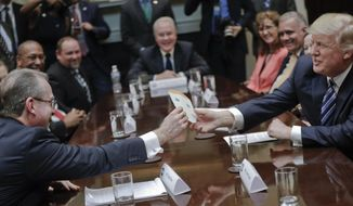 President Donald Trump takes card from Greg Knox's, left, written by his son, during a meeting on healthcare in the Roosevelt Room of the White House in Washington, Monday, March 13, 2017. (AP Photo/Pablo Martinez Monsivais)