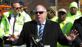 Maryland Gov. Larry Hogan stands with State Highway Administration employees in front of a salt barn in Annapolis, Maryland, on Monday, March, 13, 2017, as the state prepares for a powerful nor'easter in the forecast for the mid-Atlantic to parts of the Northeast. (AP Photo/Brian Witte)