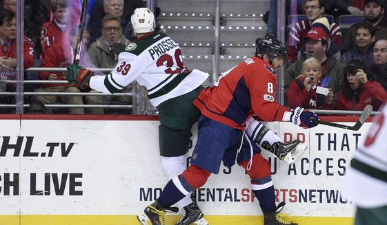 Washington Capitals left wing Alex Ovechkin (8), of Russia, slams Minnesota Wild defenseman Nate Prosser (39) into the boards during the first period of an NHL hockey game, Tuesday, March 14, 2017, in Washington. (AP Photo/Nick Wass)