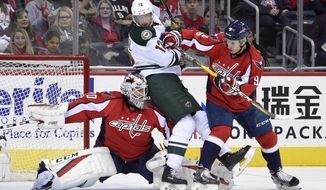 Minnesota Wild center Eric Staal (12) gets stuck between Washington Capitals goalie Braden Holtby (70) and defenseman Dmitry Orlov (9), of Russia, during the first period of an NHL hockey game, Tuesday, March 14, 2017, in Washington. (AP Photo/Nick Wass)