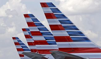 FILE - This July 17, 2015, file photo shows the tails of four American Airlines passenger planes parked at Miami International Airport, in Miami. On Tuesday, March 14, 2017, American said it will offer free meals to everyone in economy on certain cross-country flights starting May 1, 2017. The decision at the world's biggest airline copies Delta Air Lines, which announced a month earlier that it would restore free meals in economy on a dozen long-haul U.S. routes in spring 2017. (AP Photo/Alan Diaz, File)