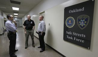 In this Friday, March 10, 2017, photo, from left Russell Nimmo, FBI supervisory special agent, and FBI agent Paul Healy talk with Oakland police detective Brad Baker outside the offices of the Oakland Safe Streets Task Force in Oakland, Calif. The federal government already plays a big role in fighting violent crime in cities, through grants and partnerships. Ten FBI agents now share an office with Oakland detectives, offering help gathering evidence, collecting DNA, chasing leads and bringing federal prosecutions that carry longer sentences in far-away prisons. (AP Photo/Eric Risberg)