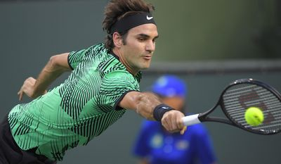 Roger Federer, of Switzerland, returns a shot to Steve Johnson at the BNP Paribas Open tennis tournament, Tuesday, March 14, 2017, in Indian Wells, Calif. (AP Photo/Mark J. Terrill)