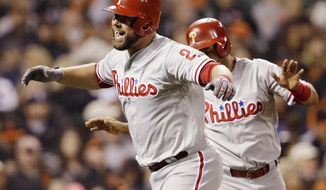 FILE- In this June 25, 2016, file photo, Philadelphia Phillies' Cameron Rupp, left, celebrates after hitting a two-run home run against the San Francisco Giants during the seventh inning of a baseball game in San Francisco. Rupp is a fan favorite in Philadelphia until football season starts. Rupp grew up in Dallas and loves the Cowboys. That doesn't sit well in Philly where Eagles fans are obsessed with hating America's Team. (AP Photo/Marcio Jose Sanchez, File)