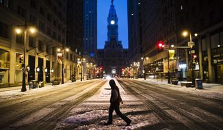 A man crosses South Broad Street in view of City Hall during a winter storm in Philadelphia, Tuesday, March 14, 2017. (AP Photo/Matt Rourke)