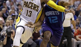 Indiana Pacers forward Paul George (13) is fouled by Charlotte Hornets guard Treveon Graham (12) during the second half of an NBA basketball game in Indianapolis, Wednesday, March 15, 2017. The Pacers defeated the Hornets 98-77. (AP Photo/Michael Conroy)