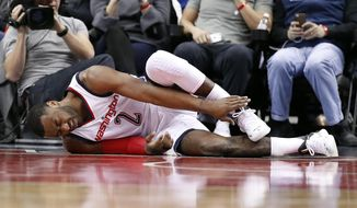 Washington Wizards guard John Wall (2) holds his foot in pain during the first half of an NBA basketball game against the Dallas Mavericks, Wednesday, March 15, 2017, in Washington. Wall left the game with the injury. (AP Photo/Alex Brandon)