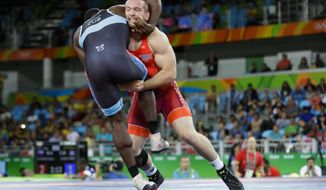 FILE - In this Aug. 21, 2016, file photo, Kyle Snyder, of the United States, in red, competes against Cuba's Javier Cortina Lacerra during the men's 97-kg freestyle wrestling competition at the 2016 Summer Olympics in Rio de Janeiro, Brazil. Ohio State, Oklahoma State and Penn State enter this year's NCAA Championships with realistic shots at the team title. The Nittany Lions are searching for their sixth in seven years _ but the Buckeyes beat them in the Big Tens. (AP Photo/Markus Schreiber, File)