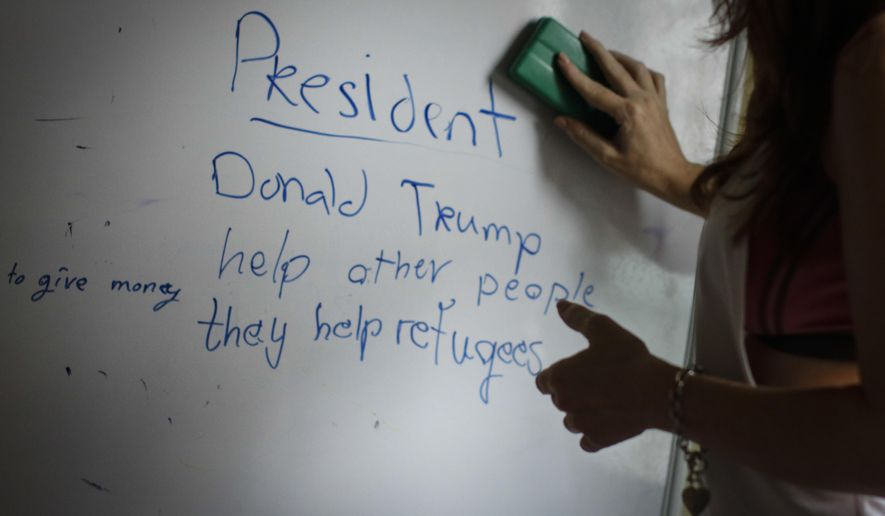 In this March 11, 2017, photo, a volunteer teacher erases the board after her English lesson after teaching Christian Burmese refugees in Kuala Lumpur, Malaysia. An Associated Press analysis suggests that the people hurt most by President Donald Trump's planned deep cuts in refugee visas are from not any of the six Muslim countries listed in his travel ban, but Myanmar. (AP Photo/Joshua Paul)