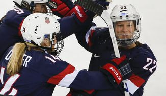 FILE - In this Feb. 17, 2014, file photo, Kacey Bellamy of the United States, right, is congratulated by teammates after scoring a goal against Sweden during the first period of the 2014 Winter Olympics women's semifinal ice hockey game  in Sochi, Russia. The U.S. women's hockey team is threatening to boycott the world championships because of a wage dispute. The team announced Wednesday that they will not participate in the International Ice Hockey Federation tournament that begins March 31, 2017, in Plymouth, Michigan. (AP Photo/Julio Cortez, File)