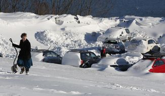 Mariah Cunningham-Kanaus walks home after digging her car out in a parking area on the eastern promenade, Wednesday, March 15, in Portland, Maine. A powerful nor'easter buffeted much of the Northeast with blizzard conditions on Tuesday. (AP Photo/Robert F. Bukaty)