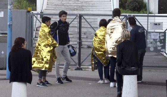 "School children, wrapped in blankets, wait nearby their high school in Grasse, southern France, after a 16-year-old student opened fire, wounding two other students and the principal trying to intervene, Thursday, March 16, 2017. French Education Minister Najat Vallaud-Belkacem says the shooting in a high school appears to be the ""insane act of a fragile young man fascinated by weapons."" (AP Photo/Philippe Farjon)"