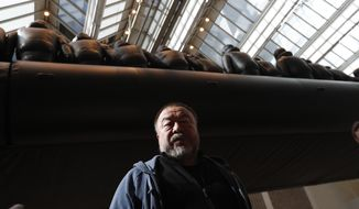 """Chinese activist and artist Ai Weiwei poses by his installation displayed at the National Gallery in Prague, Czech Republic, Thursday, March 16, 2017. A 70-metre-long inflatable boat with life-size figures of 258 refugees prepared for the gallery, called """"The Law of the Journey,"""" is one of the artists biggest work of art so far. (AP Photo/Petr David Josek)"""