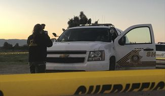 A San Bernardino County Sheriff's Department investigator takes a photo of a deputy's squad SUV after a shooting on Thursday, March 16, 2017 in Hesperia, Calif.   A Southern California sheriff's deputy was shot by a suspect who returned to the scene of a robbery and assault at a gas station convenience store, authorities said.The deputy's body armor stopped at least one bullet and he suffered only minor injuries, according to San Bernardino County Sheriff's Department spokeswoman Danielle Larsen. Several other shots shattered the windshield of a sheriff's department SUV.  (Jose Quintero/The Daily Press via AP)