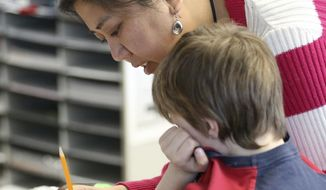 Maria Hiyas Quelle, a para teacher with Rochester Public Schools, she helps a student with a worksheet on fractions in a 2nd grade class at Jefferson Elementary School in Rochester, Minn., Tuesday, March 14, 2017. (Scott Jacobson/The Rochester Post-Bulletin via AP)