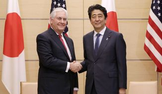 "U.S. Secretary of State Rex Tillerson, left, and Japanese Prime Minister Shinzo Abe, right, shake hands during their meeting at the prime minister's office in Tokyo, Thursday, March 16, 2017.  Tillerson said Thursday cooperation with allies Japan and South Korea is ""critical"" to addressing the threat from North Korea's nuclear and missile programs.(AP Photo/Eugene Hoshiko, Pool)"