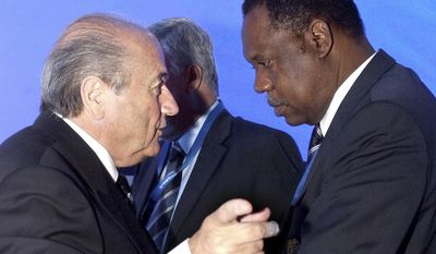 FILE - This is a Friday, May 21, 2004  file photo of FIFA President Sepp Blatter, left, as he speaks with vice-president Issa Hayatou on the second day of the 54th FIFA congress in Paris . Issa Hayatou on Thursday March 16, 2017  was voted out as president of the African soccer confederation after 29 years and will be replaced by Ahmad of Madagascar. Hayatou will also lose his position as a FIFA vice president and his place on the body's ruling council. (AP Photo/Jacques Brinon, File)