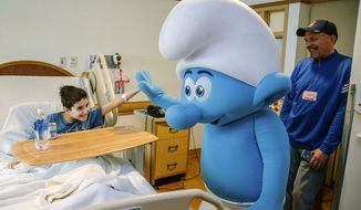 "A performer dressed as Hefty Smurf gives a high-five to Jack Gall, 13, as John Gall, right, looks on at Children's Hospital in the Lawrenceville section of Pittsburgh, Pa. on March 17, 2017. Actor and Pittsburgh native Joe Manganiello, not pictured, visited patients the hospital with Hefty, the character he voices in ""Smurfs: The Lost Village."" Manganiello also hosted a screening of the film at the hospital prior to its April 7 nationwide release. Gall's father John is also pictured. (Andrew Rush/Pittsburgh Post-Gazette via AP)"