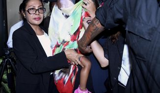 Security guards and a lawyer escort Stella Schaefer, center, covered with a scarf, the two-year-old daughter of Heather Mack, an American woman convicted in her mother's death in Indonesia, as the baby leaves Kerobokan Prison with Australian Balinese woman Oshar Putu Melody Suartama, also partially covered by the scarf, who will take care of her until her mother is released, in Bali, Indonesia Friday, March 17, 2017. Under Indonesian law, Mack has been allowed to live with her daughter at her prison's cell until Schaefer reaches the maximum age of two-year-old. (AP Photo/Firdia Lisnawati)