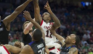 Cincinnati forwad Gary Clark, center, goes to the basket over Kansas State foreword Xavier Sneed, left, during the first half of a first-round game of the men's NCAA college basketball tournament in Sacramento, Calif., Friday, March 17, 2017. (AP Photo/Bryan Patrick)