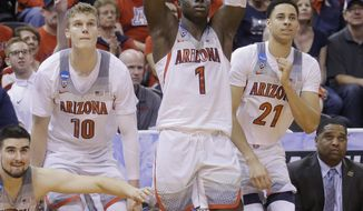 Arizona's Lauri Markkanen (10), Rawle Alkins (1) and Chance Comanche (21) celebrate on the bench during the second half of the team's first-round game against North Dakota in the NCAA men's college basketball tournament Thursday, March 16, 2017, in Salt Lake City. Arizona won 100-82. (AP Photo/Rick Bowmer)