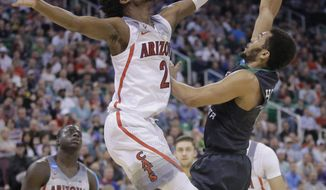 Arizona guard Kobi Simmons (2) blocks a shot by North Dakota guard Quinton Hooker, right, during the first half of a first-round men's college basketball game in the NCAA tournament Thursday, March 16, 2017, in Salt Lake City. (AP Photo/Rick Bowmer)