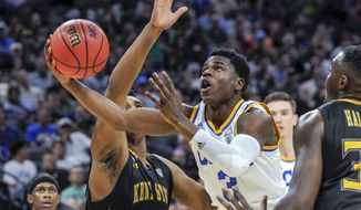 UCLA guard Aaron Holiday, right, drives to the basket against Kent State center Adonis De La Rosa, left, during the second half of a first-round game of the men's NCAA college basketball tournament in Sacramento, Calif., Friday, March 17, 2017. UCLA won 97-80. (AP Photo/Bryan Patrick )