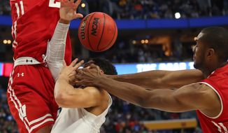 Villanova guard Josh Hart (3) drives to the basket against Wisconsin forward Ethan Happ (22) and forward Vitto Brown (30) with three seconds remaining in the second half of a second-round men's college basketball game in the NCAA Tournament, Saturday, March 18, 2017, in Buffalo, N.Y.  A Villanova foul was called on the play and Wisconsin won, 65-62. (AP Photo/Bill Wippert)