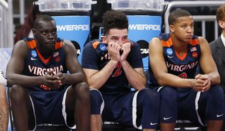 Virginia forward London Perrantes, center, guard Marial Shayok, left, and guard Devon Hall watch from the bench during the final seconds of a second-round game of the NCAA men's college basketball tournament against Florida, Saturday, March 18, 2017, in Orlando, Fla. Florida defeated Virginia 65-39. (AP Photo/Wilfredo Lee)