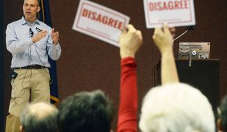 "Audience members hold signs reading, ""DISAGREE"" as U.S. Rep. Scott Perry, R-Pa., speaks during a town hall meeting Saturday, March 18, 2017 in Red Lion, Pa. Perry's event turned contentious in his conservative south-central Pennsylvania district over questions about his support for President Donald Trump's budget proposal and immigration plans and for undoing former President Barack Obama's signature health care law. (AP Photo/Marc Levy)"