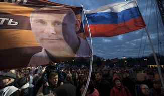 A flag with the portrait of Russian President Vladimir Putin waves over the crowd during the Vesna (Sping) festival commemorating the annexation, in Moscow, Russia, Saturday, March 18, 2017. Residents of cities in Crimea and Russia held gatherings to commemorate the third anniversary of Russia's annexation of the Black Sea peninsula from Ukraine. (AP Photo/Ivan Sekretarev)