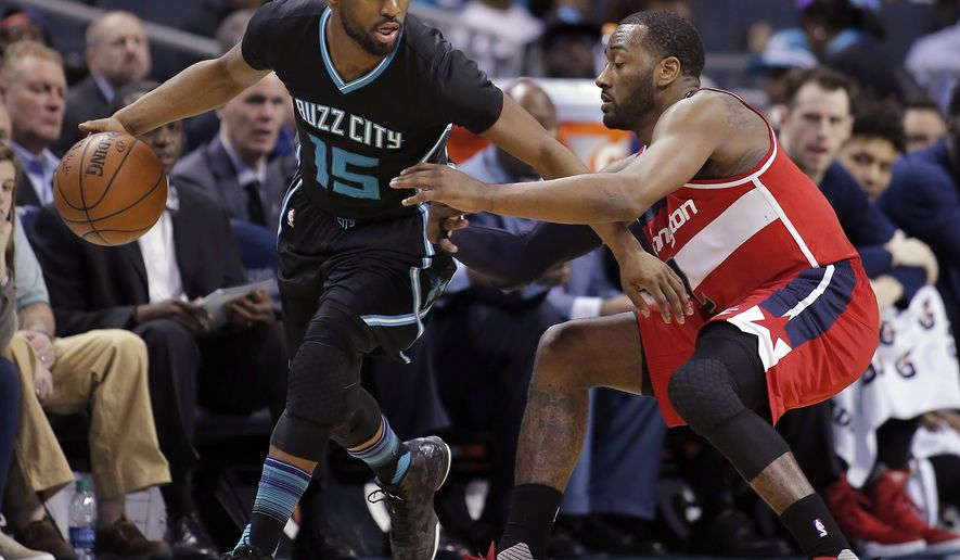 Charlotte Hornets' Kemba Walker (15) looks to dribble away from Washington Wizards' John Wall (2) during the second half of an NBA basketball game in Charlotte, N.C., Saturday, March 18, 2017. The Hornets won 98-93. (AP Photo/Bob Leverone)