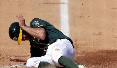 Oakland Athletics' Adam Rosales slides safely under the throw to score on a wild pitch against the San Diego Padres during the third inning of a spring training baseball game, Saturday, March 18, 2017, in Mesa, Ariz. (AP Photo/Matt York)