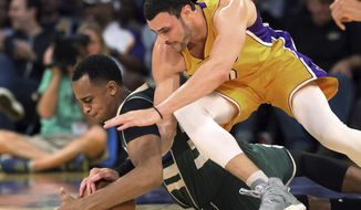 Milwaukee Bucks center John Henson, left, and Los Angeles Lakers forward Larry Nance Jr. tangle on the floor during the first half of an NBA basketball game in Los Angeles on Friday, March 17, 2017. (AP Photo/Reed Saxon)