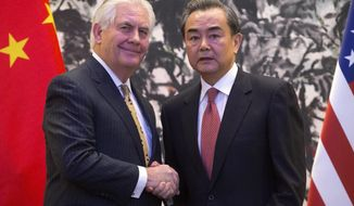 U.S. Secretary of State Rex Tillerson, left, and Chinese Foreign Minister Wang Yi shake hands at the end of a joint press conference following their meeting at the Diaoyutai State Guesthouse in Beijing, China, Saturday, March 18, 2017. Tillerson arrived in Beijing on Saturday for his first face-to-face talks with Chinese leaders expected to focus on North Korea's nuclear program, trade and South China Sea territorial disputes. (AP Photo/Mark Schiefelbein, Pool)
