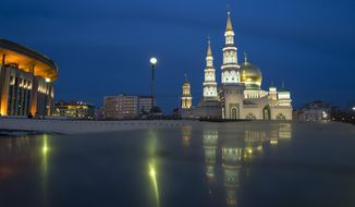 In this photo taken on Sunday, March 12, 2017, the minarets of the Moscow Cathedral Mosque, right, rise next to an sport arena built for the 1980 Moscow Olympics in Moscow, Russia. For an Associated Press correspondent returning to the Russian capital on an extended assignment for the first time since the early 1990s,  the city holds many new landmarks, but some sights remain unchanged as well.  (AP Photo/Alexander Zemlianichenko)