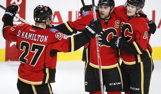 Calgary Flames' Mark Giordano, center, celebrates his goal with teammates Dougie Hamilton, left, and Matthew Tkachuk against the Dallas Stars during the second period of an NHL hockey game in Calgary, Alberta, Friday, March 17, 2017. (Jeff McIntosh/The Canadian Press via AP)