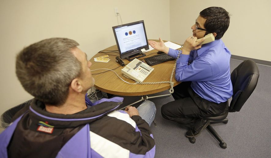 Luis Rios helps a customer buy health insurance in Utah, where officials are reviewing the effects of the House Republicans' plan. (Associated Press)