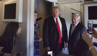 President Donald Trump talks to the press corps inside Air Force One at the Palm Beach International Airport, Sunday, March 19, 2017, in West Palm Beach, Fla. Trump is returning to Washington. Standing next to Trump  is New England Patriots owner Robert Kraft.  (AP Photo/Manuel Balce Ceneta)