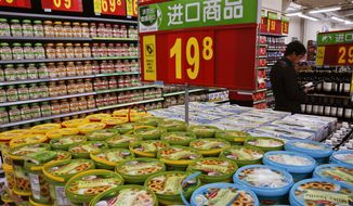 In this Tuesday, March 14, 2017 photo, a man looks at imported wines on display for sale near the imported cookies and nuts, at Walmart in Beijing. China's trading partners are bringing the top U.N. food standards official to Beijing in a last-ditch attempt to persuade regulators to scale back plans for intensive inspections of food imports - including such low-risk items as wine and chocolate - that Washington and Europe say could disrupt billions of dollars in trade. (AP Photo/Andy Wong)