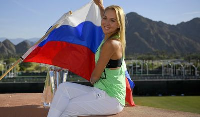 Elena Vesnina, of Russia, poses with the trophy and a Russian flag after her win against Svetlana Kuznetsova, of Russia, in the women's final at the BNP Paribas Open tennis tournament, Sunday, March 19, 2017, in Indian Wells, Calif. (AP Photo/Mark J. Terrill)