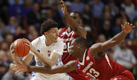 North Carolina's Justin Jackson, left, is trapped by Arkansas' Moses Kingsley, right, and Manuale Watkins, back, during the first half in a second-round game of the NCAA men's college basketball tournament in Greenville, S.C., Sunday, March 19, 2017. (AP Photo/Chuck Burton)