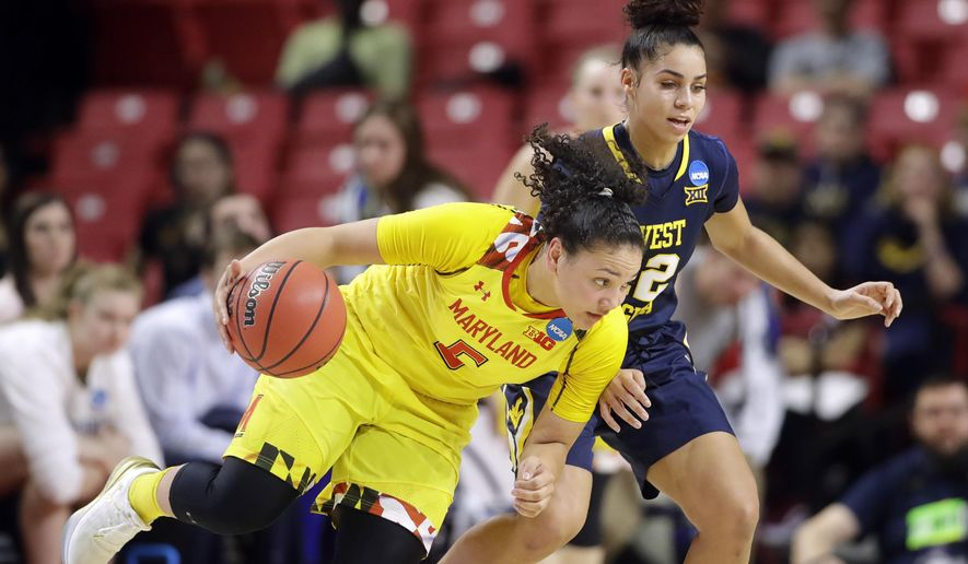 Maryland guard Destiny Slocum, left, drives around West Virginia guard Chania Ray in the first half of a second-round game in the women's NCAA college basketball tournament in College Park, Md., Sunday, March 19, 2017. (AP Photo/Patrick Semansky)