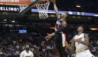 Portland Trail Blazers' Damian Lillard (0) dunks over Miami Heat's James Johnson (16) and Hassan Whiteside (21) during the first half of an NBA basketball game, Sunday, March 19, 2017, in Miami. (AP Photo/Lynne Sladky)