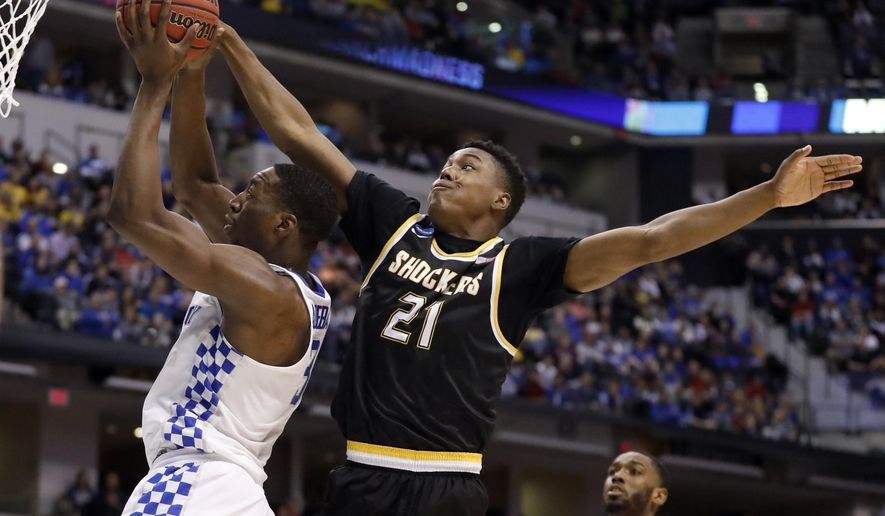 Kentucky's Bam Adebayo, left, heads to the basket as Wichita State's Darral Willis Jr. (21) defends during the first half of a second-round game in the men's NCAA college basketball tournament Sunday, March 19, 2017, in Indianapolis. (AP Photo/Jeff Roberson)