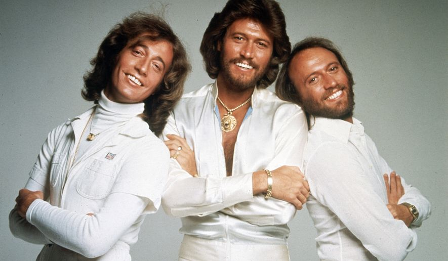British pop group the Bee Gees pose for photographers, somewhere in England, Jan. 1979. From left to right; Robin Gibb, Barry Gibb and Maurice Gibb. (AP Photo/HO)