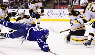 Toronto Maple Leafs right wing Connor Brown (12) dives for the puck as Boston Bruins defenseman Torey Krug (47), goalie Tuukka Rask (40) and defenseman Adam McQuaid (54) watch during the second period of an NHL hockey game Monday, March 20, 2017, in Toronto. (Frank Gunn/The Canadian Press via AP)