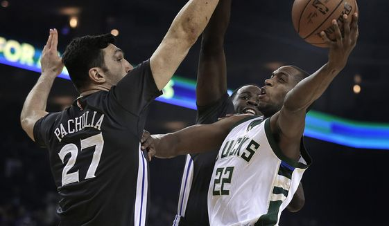 Milwaukee Bucks' Khris Middleton, right, shoots over Golden State Warriors' Zaza Pachulia (27) and Draymond Green during the first half of an NBA basketball game Saturday, March 18, 2017, in Oakland, Calif. (AP Photo/Ben Margot)