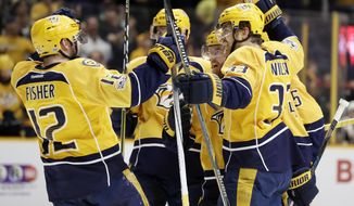 Nashville Predators' Mike Fisher (12) and Colin Wilson (33) celebrate with defenseman Ryan Ellis, second from right, after Ellis scored a goal against the Arizona Coyotes during the second period of an NHL hockey game Monday, March 20, 2017, in Nashville, Tenn. (AP Photo/Mark Humphrey)